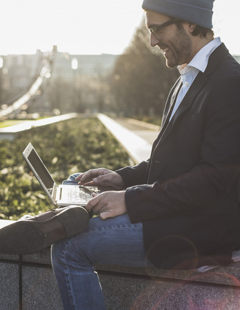 work life balance: Germany, Frankfurt, Young businessman sitting on wall using laptop LANG_EVOIMAGES