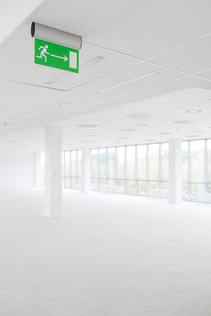 emergency exits: Signo de ruta de escape en una habitación de oficina blanca vacía