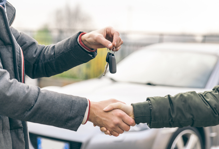handclasp: Two people reaching an agreement about a car sale LANG_EVOIMAGES