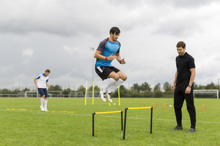 analytic: Coach exercising with soccer players on sports field