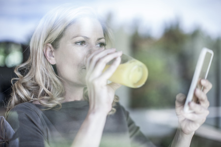 Woman drinking juice looking at cell phone