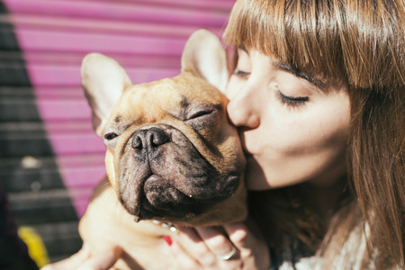 Portrait of young woman kissing French bulldog LANG_EVOIMAGES