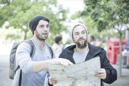 Young men in the city with map looking for directions LANG_EVOIMAGES