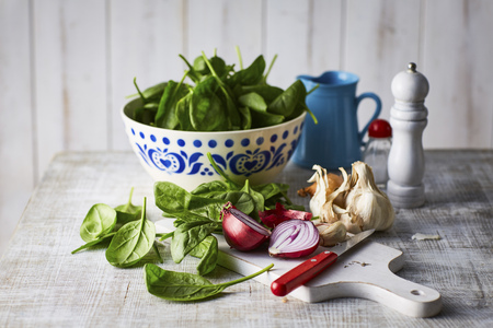 Fresh spinach leaves, red onion and garlic on chopping board, knife