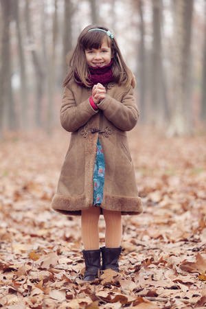 Young girl, brown coat in park, autum, smiling, hands folded