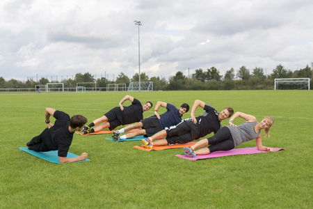 Coach doing exercises with team on sports field