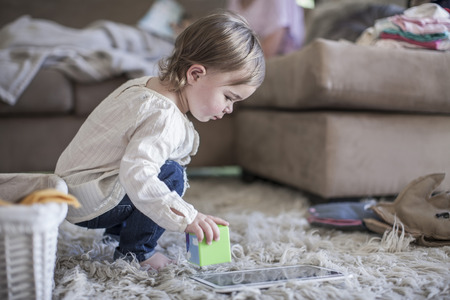 cowering: Baby girl playing with building blocks in living room LANG_EVOIMAGES