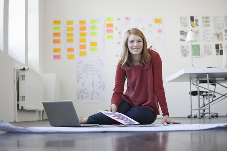 open floor plan: Young woman in office sitting on floor working through papers