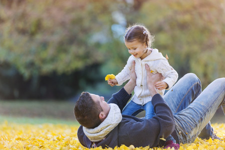 Happy father with daughter in autumn leaves LANG_EVOIMAGES