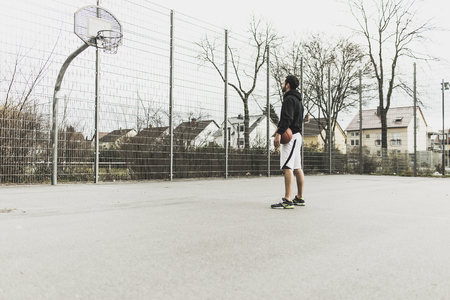 Young basketball player in front of basketball hoop LANG_EVOIMAGES