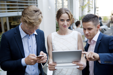 waist down: Three young businesspeople with digital tablet and cell phone outdoors