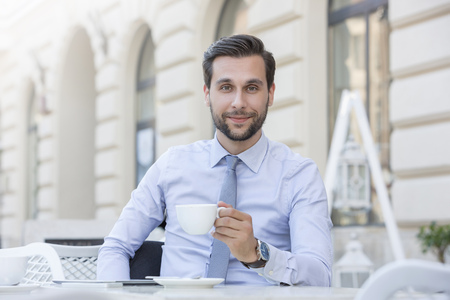 Portrait of smiling young businessman sitting at sidewalk cafe with cup of coffee LANG_EVOIMAGES