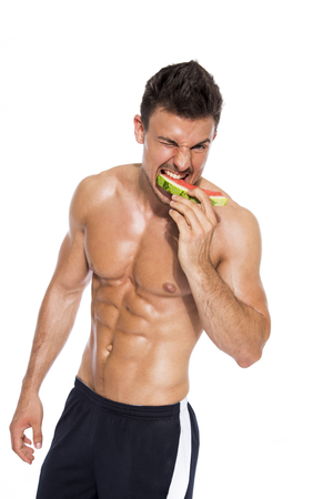 Shirtless muscular man biting slices of watermelon in front of white background LANG_EVOIMAGES