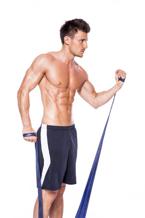 Shirtless muscular man training with fitness band in front of white background