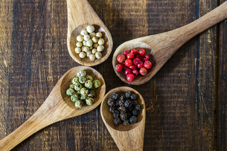 Four wooden spoons of different peppercorns
