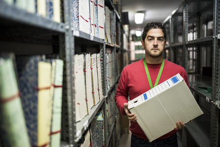 Portrait of serious looking man holding folder in an archive LANG_EVOIMAGES