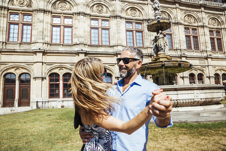 looking for love: Austria, Vienna, smiling couple dancing Viennese waltz in front of state opera LANG_EVOIMAGES