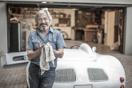 analytic: Smiling senior man with cleaning cloth leaning at sports car LANG_EVOIMAGES