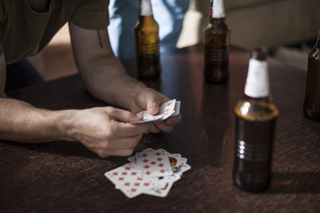 Young man holding playing cards on table with beer bottles LANG_EVOIMAGES