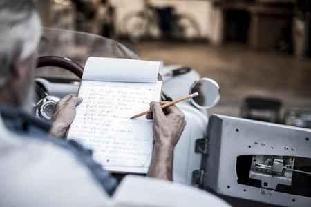 Senior homme avec liste de contrôle dans la voiture de sport LANG_EVOIMAGES
