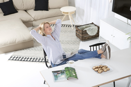 living room sofa: Woman relaxing with feet up on the table in her living room