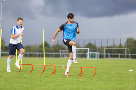 Two soccer players exercising on sports field