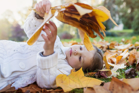Girl lying in autumnal meadow holding leaves