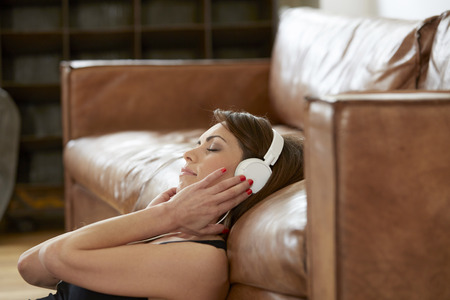 living room sofa: Smiling woman with closed eyes leaning against leather couch hearing music with headphones