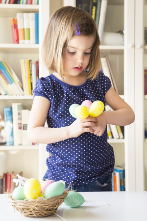 decorating: Little girl with Easter eggs