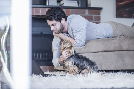 living room sofa: Man with dog lying on couch looking at laptop