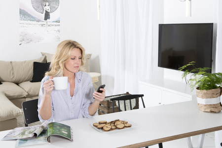 living room sofa: Woman sitting at the table in her living room holding smartphone and coffee cup