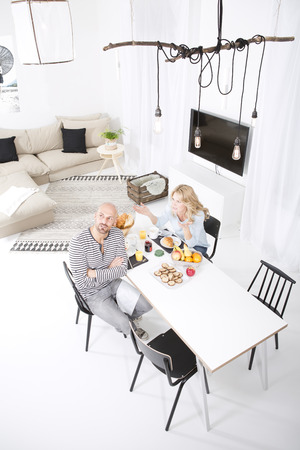 living room sofa: Mature couple quarreling at breakfast table LANG_EVOIMAGES