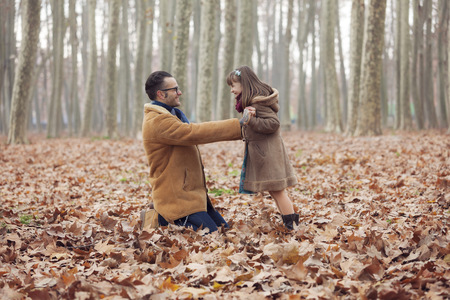 Father playing with his daughter in park, autumn