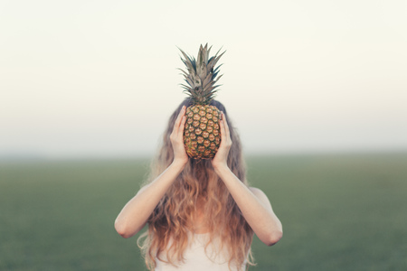 obscuring: Blonde woman holding pineapple
