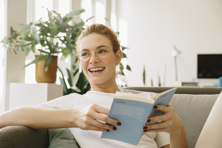 living room sofa: Young woman at home, looking up from her book, laughing LANG_EVOIMAGES