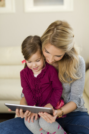 living room sofa: Mother and her little daughter looking at digital tablet