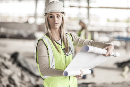 incidental people: Woman in protective workwear holding building plan in construction site
