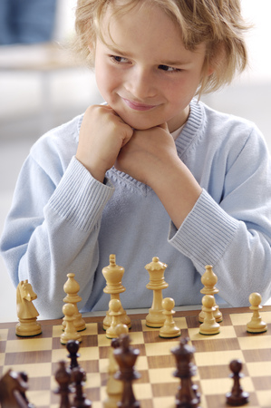 Portrait of smiling little boy playing chess