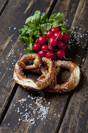 Two pretzels, red radishes and scattered salt grains on dark wood