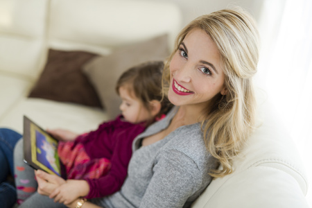 living room sofa: Portrait of smiling woman sitting with her little daughter on couch in the living room