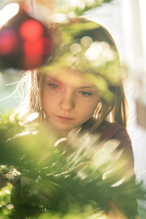 decorating: Portrait of girl decorating Christmas tree LANG_EVOIMAGES