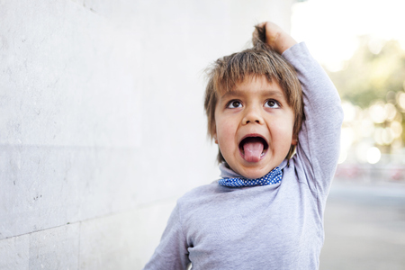 Little boy sticking out tongue while pulling funny face