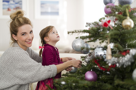 decorating: Portrait of smiling woman decorating Christmas tree with her little daughter in the living room