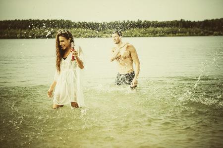 Germany, Haltern, friends standing in water of Lake Silbersee having fun