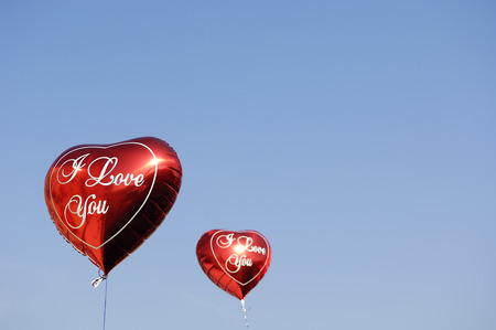 decorating: Two red heart-shaped balloons in front of blue sky LANG_EVOIMAGES