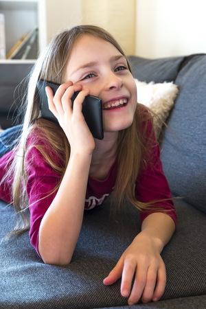 living room sofa: Portrait of smiling girl lying on the couch telephoning with phablet LANG_EVOIMAGES