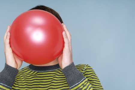 Teenage boy hiding face behind red balloon in front of blue background LANG_EVOIMAGES