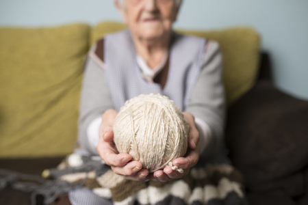living room sofa: Hands of senior woman holding ball of wool LANG_EVOIMAGES
