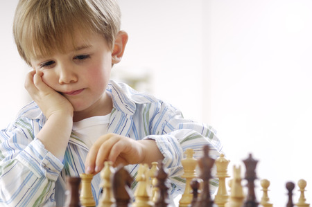 pondering: Portrait of thinking little boy playing chess