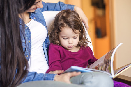 sit down: Portrait of little girl watching childrens book with her mother